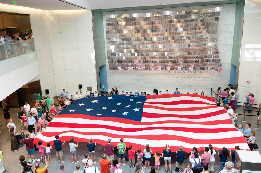 museum visitors unfold student made replica of the Star Spangled Banner